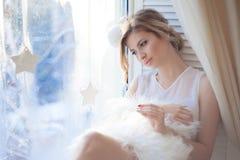 Ungt härligt flickasammanträde på fönsterbrädan som ut ser fönstret, morgonljus, ilsken blick arkivfoton