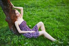 Ungt härligt flickasammanträde på gräs Fotografering för Bildbyråer