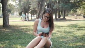 Ungt härligt flickasammanträde på gräsmatta parkerar in genom att använda minnestavlaPC:N, on-line shoppingbegrepp royaltyfri fotografi