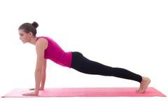 Ungt härligt göra för kvinna skjuter upp övning på matt isolat för yoga Royaltyfri Fotografi