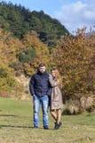 Ungt härligt gift par mot bakgrunden av höstskogen på en närbild för solig dag arkivbild