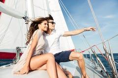 Ungt härligt gift par som omfamnar på yachten royaltyfria bilder