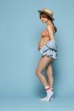 Ungt härligt gravid kvinnaanseende på blå bakgrund fotografering för bildbyråer