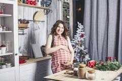 Ungt härligt gravid med hemma in le för kök arkivbilder