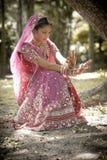 Ungt härligt indiskt hinduiskt brudsammanträde under träd royaltyfri fotografi