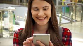 Ungt härligt kvinnaanseende, i att le för shoppinggalleria Använda hennes smartphone som talar med vänner lager videofilmer