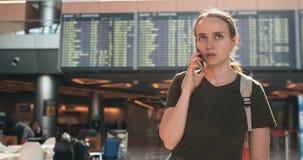Ungt härligt kvinnaanseende på flygplatsen som kallar på telefonen lager videofilmer
