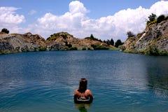 Ungt härligt kvinnamodellanseende i en sjö av ett gammalt sandmining ställe på ferie i Spanien royaltyfria foton
