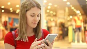 Ungt härligt kvinnasammanträde, i att le för shoppinggalleria Använda hennes smartphone som pratar med vänner lager videofilmer