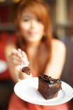Ungt härligt kvinnasammanträde i cafen som äter chokladtårtan Royaltyfri Fotografi