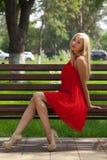 Ungt härligt kvinnasammanträde på en bänk i sommaren parkerar royaltyfria bilder