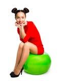 Ungt härligt kvinnasammanträde på en stor grön boll fotografering för bildbyråer