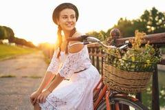 Ungt härligt kvinnasammanträde på hennes cykel med blommor på solen royaltyfri bild