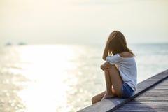 Ungt härligt kvinnasammanträde på pir som tycker om solnedgång Fotografering för Bildbyråer