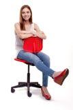 Ungt härligt kvinnasammanträde på röd stol Arkivfoto