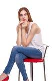 Ungt härligt kvinnasammanträde på röd stol Royaltyfria Bilder