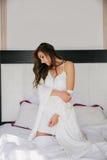 Ungt härligt kvinnasammanträde på säng hemma Arkivbild