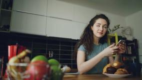 Ungt härligt lockigt nätt caucasian kvinnasammanträde på tabellen i trevligt kök genom att använda smartphonen, smsar hon någon stock video