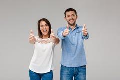 Ungt härligt posera för gift par som bra visar över grå bakgrund arkivfoto