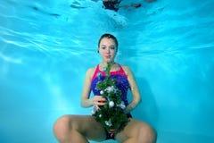 Ungt härligt sitta för flicka som är undervattens- på botten av pölen i luftbubblorna med en leksak i hans hand, och se kammen Royaltyfri Bild