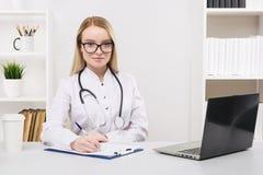 Ungt h?rligt arbeta f?r doktorskvinna som ?r lyckligt, och leende i sjukhuset som sitter p? tabellen arkivbilder
