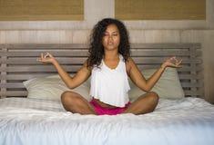 Ungt hemmastatt sovrum för attraktiv och lycklig svart afro amerikansk kvinna som gör yogameditation och sträckning för kroppavko royaltyfria bilder