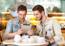 Ungt hipstergrabbsammanträde i ett kafé som pratar och dricker coffe Royaltyfria Bilder