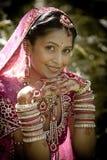 Ungt härligt indiskt hinduiskt brudsammanträde i trädgårds- utomhus Royaltyfria Bilder