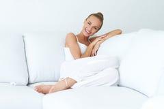 Ungt härligt kvinnasammanträde på soffan Royaltyfria Foton