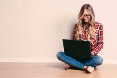 Ungt idérikt kvinnasammanträde i golvet med bärbara datorn / Tillfälligt b Royaltyfri Bild