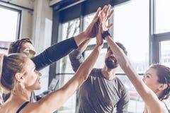 Ungt idrotts- folk i sportswearen som ger höjdpunkt fem i idrottshall Arkivbild