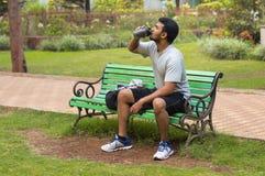 Ungt idrottsman nendricksvatten, medan vila in parkera bänken royaltyfria foton