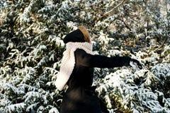 Ungt kasta för kvinna kastar snöboll Arkivbild