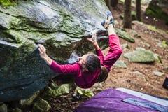 Ungt klättra för kvinnlig idrottsman nen som är utomhus- på en sten arkivfoton