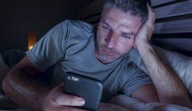 Ungt knyta kontakt för sovrum för attraktiv och avkopplad man som hemmastatt är sent - natt som ligger på säng i mörkt ljus genom arkivbilder