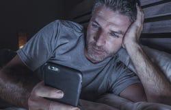 Ungt knyta kontakt för sovrum för attraktiv och avkopplad man som hemmastatt är sent - natt som ligger på säng i mörkt ljus genom fotografering för bildbyråer