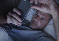 Ungt knyta kontakt för sovrum för attraktiv och avkopplad man som hemmastatt är sent - natt som ligger på säng i mörkt ljus genom arkivbild