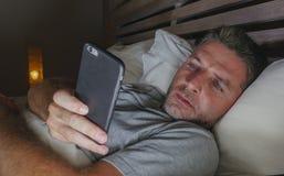 Ungt knyta kontakt för sovrum för attraktiv och avkopplad man som hemmastatt är sent - natt som ligger på säng i mörkt ljus genom arkivfoton