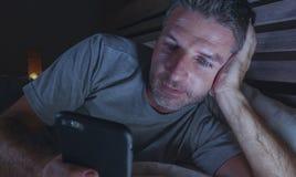 Ungt knyta kontakt för sovrum för attraktiv och avkopplad man som hemmastatt är sent - natt som ligger på säng i mörkt ljus genom royaltyfri fotografi