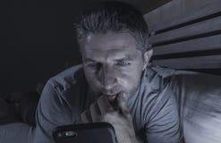 Ungt knyta kontakt för sovrum för attraktiv och avkopplad man som hemmastatt är sent - natt som ligger på säng i mörkt ljus genom arkivfoto