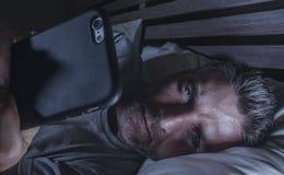 Ungt knyta kontakt för sovrum för attraktiv och avkopplad man som hemmastatt är sent - natt som ligger på säng i mörkt ljus genom royaltyfria foton