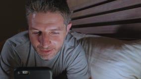 Ungt knyta kontakt för sovrum för attraktiv och avkopplad man som hemmastatt är sent - natt som ligger på säng i mörkt ljus genom lager videofilmer