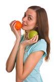 Ungt kvinnaholdingäpple och orange över white Royaltyfri Bild