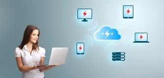 Ungt kvinnainnehav en bärbar dator och framlägga beräknande netw för moln Arkivbild