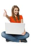Kvinnasammanträde på däcka med henne bärbar datordanande tumm upp Royaltyfri Foto