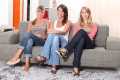 Kvinnasammanträde på en sofa Arkivfoton