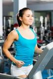 Ungt kvinnaspring på en treadmill Royaltyfria Foton