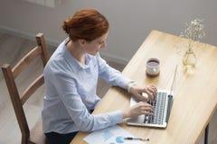 Ungt kvinnligt arbete för bästa ovannämnd sikt på datoren arkivbild