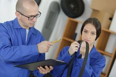 Ungt kvinnligt bälte för hållande tajming för mekaniker i lagergarage royaltyfri bild