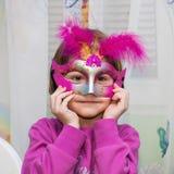 Ungt kvinnligt barn med den röda Mardi Gras maskeringen arkivbild